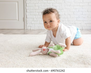 Adorable little girl playing on carpet with bunny near wet spot