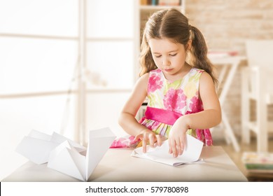 Adorable little girl playing with origami paper airplane. Little child doing paper airlpane. Children eduction concept. Kinder craft