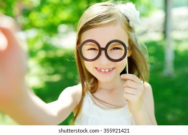 Adorable little girl playing with paper glasses on a stick on warm summer day