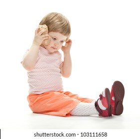 Adorable little girl playing with a seashell sitting on the floor, studio shot on white background