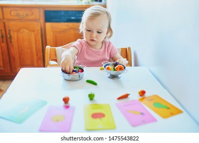 Adorable little girl playing with toy fruits and vegetables at home, in kindergaten or preschool; trying to match figurine with image on a card. Indoor creative games for kids