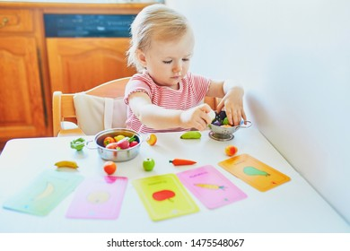 Adorable little girl playing with toy fruits and vegetables at home, in kindergaten or preschool; trying to match figurine with image on a card. Words on cards written in French.