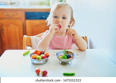 Adorable little girl playing with toy fruits and vegetables at home, in kindergaten or preschool. Indoor creative games for kids