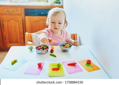 Adorable little girl playing with toy fruits and vegetables at home, in kindergaten or preschool; trying to match figurine with image on a card. Words on cards written in French