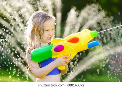 Adorable little girl playing with water gun on hot summer day. Cute child having fun with water outdoors. Funny summer games for kids.