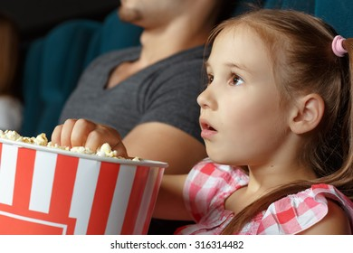 Adorable little girl with popcorn at the cinema