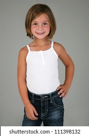Adorable Little Girl Posing with hand on hip on Grey Background