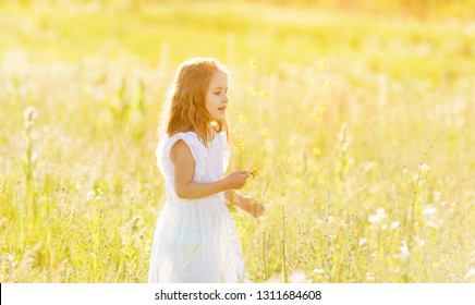 Adorable little girl posing in white dress in garden looking to the side with curiosity