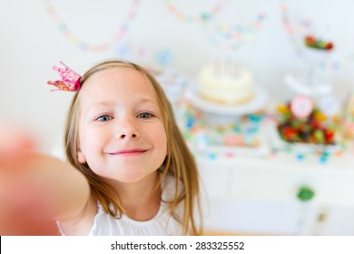 Adorable little girl with princess crown at kids birthday party making selfie