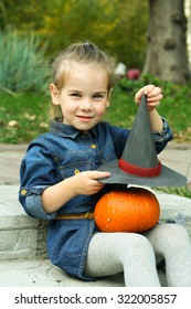Adorable little girl with a pumpkin and witches hat for Halloween outdoors at beautiful autumn day