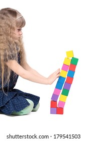 Adorable little girl push a brick toy tower isolated on white background