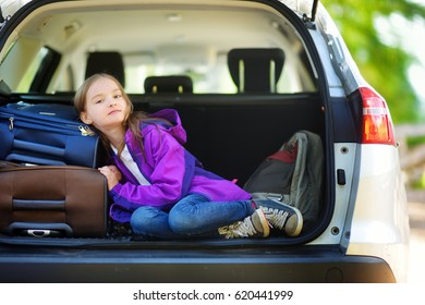 Adorable little girl ready to go on vacations with her parents. Kid relaxing in a car before a road trip. Traveling by car with kids.