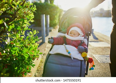 Adorable little girl in red jacket and white knitted hat and scarf sitting in pushchair outdoors on a fall or spring day