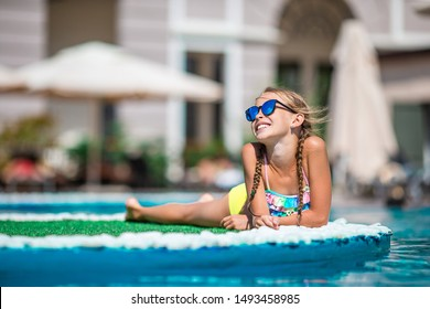 Adorable little girl relax by outdoor swimming pool