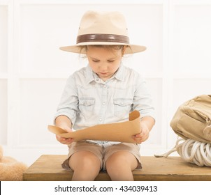 Adorable little girl in a safari hat and explorer clothes examining old treasure map