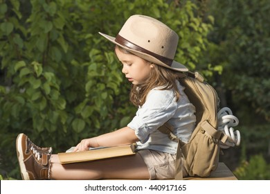 Adorable little girl in a safari hat and explorer clothes reading old book sitting in a wooden suitcase with backpack and safety rope outdoor. Children's play concept