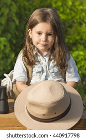 3351fa1ba35d8 Adorable little girl in a safari hat and explorer clothes playing safari  sitting on wooden suitcase