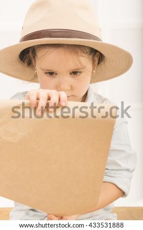 f0a84d0e6e61e Adorable little girl in a safari hat and explorer clothes examining old  treasure map