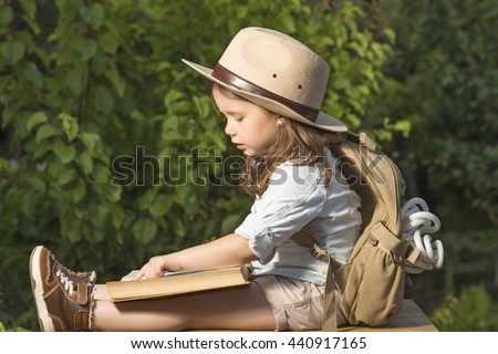 fe8f594b35168 Adorable little girl in a safari hat and explorer clothes reading old book  sitting in a