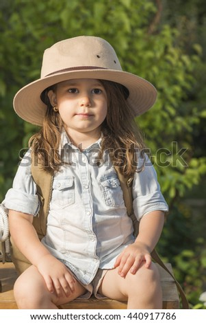 b0e38a33f82b1 Adorable little girl in a safari hat and explorer clothes playing safari  sitting on wooden suitcase