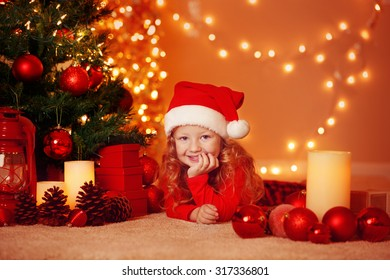 Adorable little girl with Santa Hat, gifts and decorated illuminated Christmas Tree. Greeting card or cover, with copy space