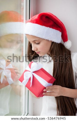 ccae29f919681 adorable little girl in Santa hat dreaming by the window holding a box with  present in