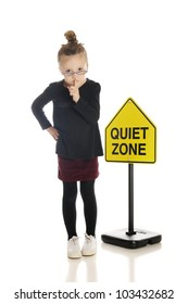 "An adorable little girl school teacher or librarian, gesturing to silence the viewer.  She stands in front of a ""Quiet Zone"" sign.  On a white background."