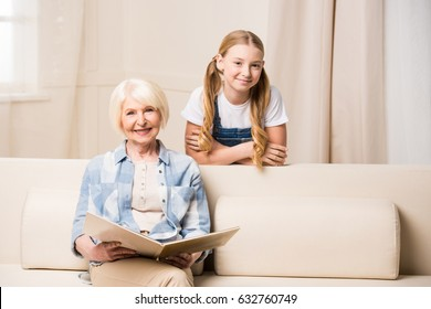 Adorable little girl and senior woman with photo album smiling at camera