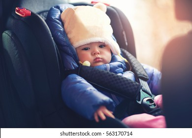 Adorable little girl sitting in car in winter clothes