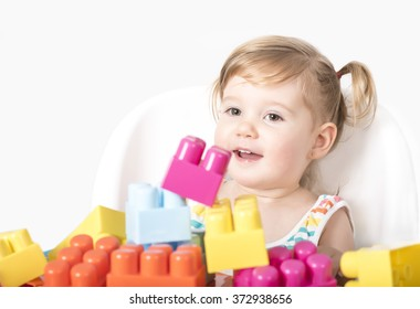 Adorable little girl sitting on chair smiling and playing with colorful toy blocks