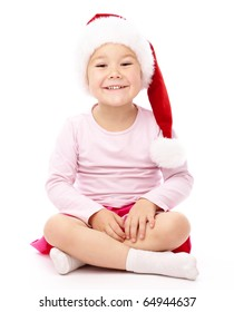 Adorable little girl is sitting on floor, wearing red Christmas cap, isolated over white