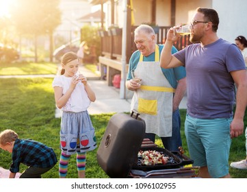 Adorable little girl in the skirt is drinking juice , while her father is drinking beer and his father is proudly looking at her.
