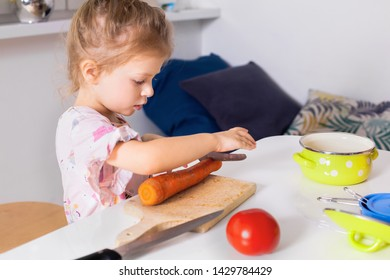 Adorable little girl slicing carrots in the kitchen.Kids helping with domestic jobs concept