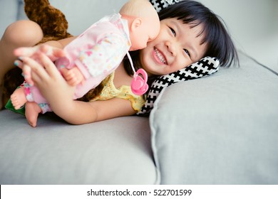 Adorable little girl smile and sleep in the sofa bed and hug her baby doll.