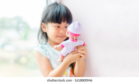 Adorable little girl smile and talking with her baby doll alone at home. Asian toddler girl role playing with the doll.Only child, imagination, Child development and comfort zone concept.