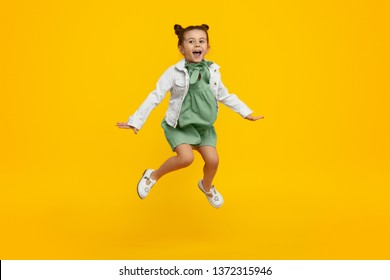 Adorable little girl in stylish dress and jacket yelling and leaping up in excitement against bright yellow background