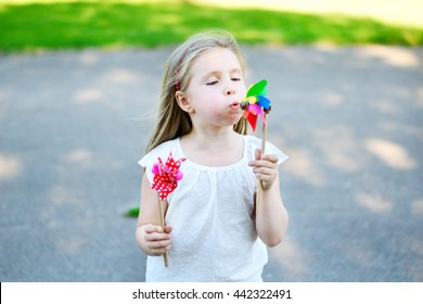 Adorable little girl in summer day holds windmill in hand