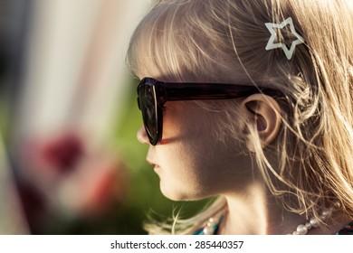 Adorable little girl in sun glasses. Bright sun. High contrast. Soft focus.