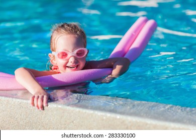 Adorable little girl swimming with a pink foam noodle in a pool while on summer vacation