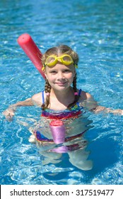 Adorable little girl swimming with a pink foam noodle in a pool