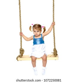 Adorable little girl swinging on a swing. She is happy to have fun and show how she can do it. The concept of summer recreation and harmonious development of the child. Isolated on white