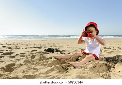 Adorable little girl takes pictures with her red camera on the beach