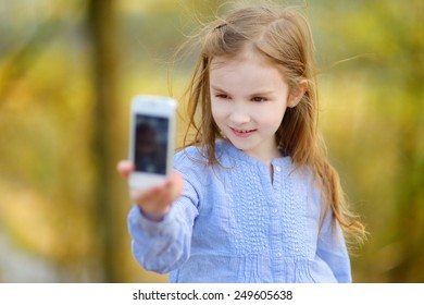 Adorable little girl taking a photo of herself on beautiful summer day