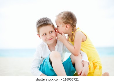 Adorable little girl telling a secret to her brother