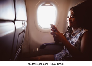 Adorable little girl traveling by an airplane child sitting by aircraft window and listen music