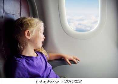 Adorable little girl traveling by an airplane. Child sitting by aircraft window and looking outside. Traveling abroad with kids.
