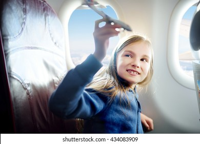 Adorable little girl traveling by an airplane. Child sitting by aircraft window and playing with toy plane.