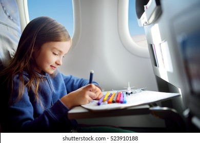 Adorable little girl traveling by an airplane. Child sitting by aircraft window and drawing a picture with colorful pencils.