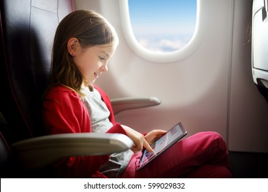 Adorable little girl traveling by an airplane. Child sitting by aircraft window and using a digital tablet during the flight.