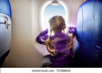 Adorable little girl traveling by an airplane. Child sitting by aircraft window and looking outside. Traveling with kids abroad.
